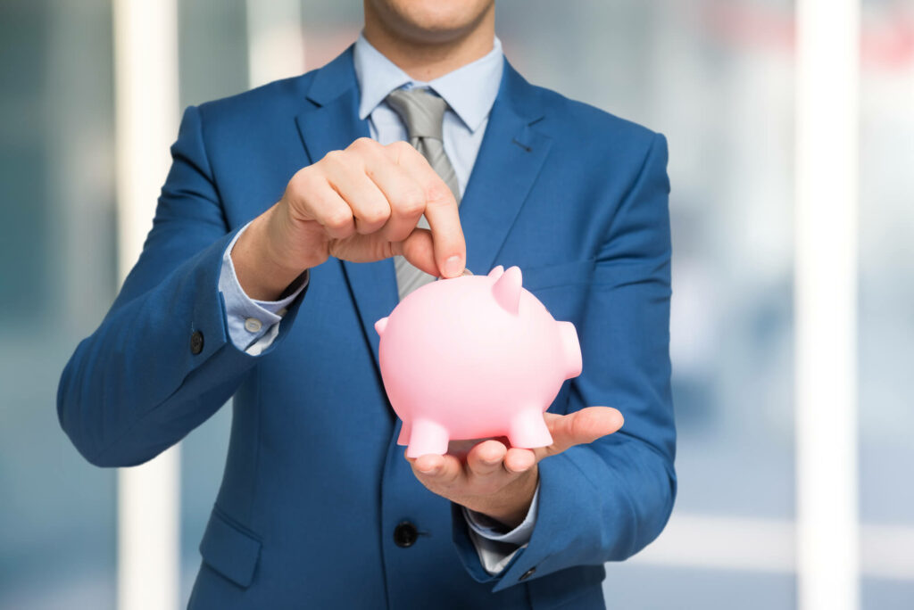 Man in suit putting money in the piggy bank